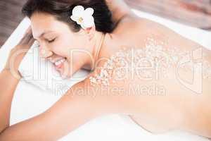 Woman lying on massage table with salt scrub on back