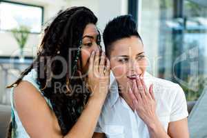 Lesbian couple whispering in ears