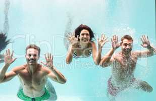 Two couples swimming underwater in swimming pool