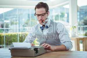 Handsome man using old fashioned typewriter