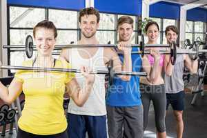 Fitness class lifting barbell