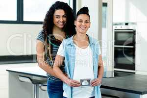 Pregnant lesbian couple holding a sonography report