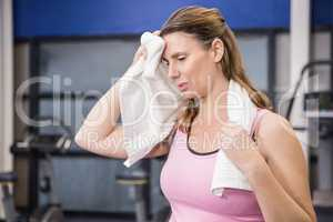 Tired pregnant woman wiping sweat with towel