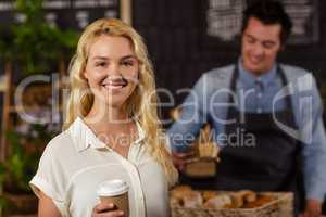 Smiling waiter serving a coffee to a customer