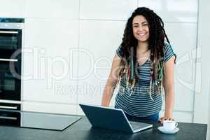 Portrait of woman leaning on worktop with laptop and tea cup in