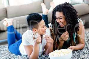 Lesbian couple lying on rug while having popcorn