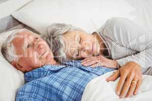 Senior man lying awake next to asleep senior woman