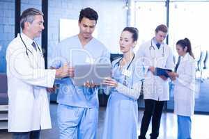 Medical team using laptop, digital tablet and examining medical