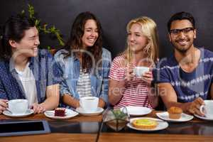 Smiling friends enjoying coffee together and using technologies