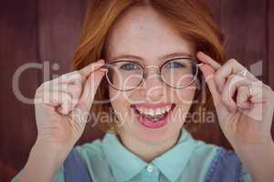 Red-haired hipster woman holding her glasses