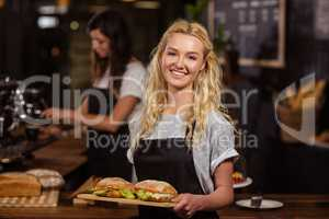 Pretty waitress holding a tray with sandwiches
