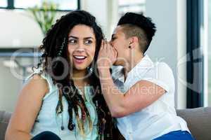 Lesbian couple whispering in ear