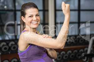 Smiling pregnant woman showing biceps