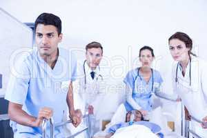 Concerned doctors standing near patient on bed