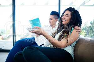 Lesbian couple watching television and reading a book
