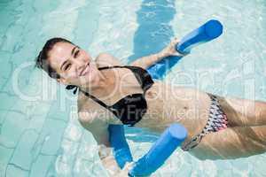 Pretty brunette in swimsuit swimming with a foam roller