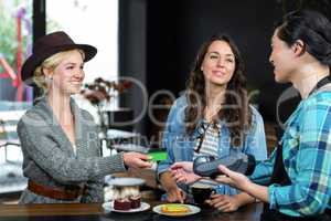 Smiling barista taking credit card from customer