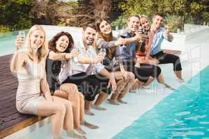 Young people sitting by swimming pool