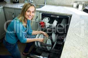 Pretty blonde woman emptying the dishwasher