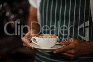 Close up of barista holding cappuccino
