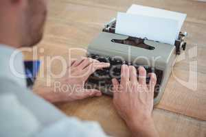 masculine hands typing on old typewriter