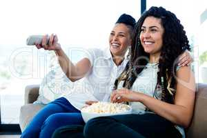 Lesbian couple watching television with a bowl of popcorn
