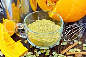 Flour pumpkin in glass cup with seeds and sieve on board
