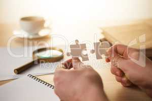 Building a business success. The hands with puzzles