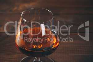 Glass of cognac on the wooden table.