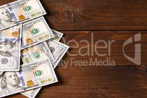 new 100 US dollars bills on wooden background