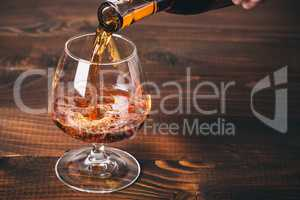 Pouring cognac or whiskey from the bottle into the glass against wooden background