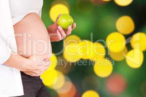 Composite image of midsection of pregnant woman holding green ap