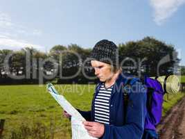 Composite image of backpacker looking a map