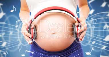 Composite image of pregnant woman holding earphones over bump