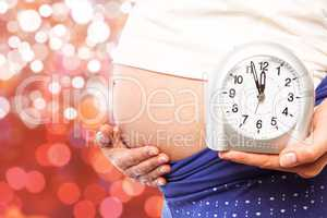Composite image of pregnant woman showing clock and bump