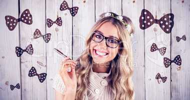 Composite image of gorgeous smiling blonde hipster holding pen
