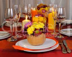Autumn flowers in a vase on the table with pumpkin