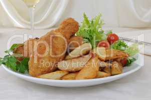 Chicken drumsticks with breadcrumbs with potatoes and salad