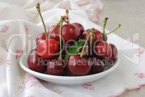 plate of ripe cherries on the table with a napkin