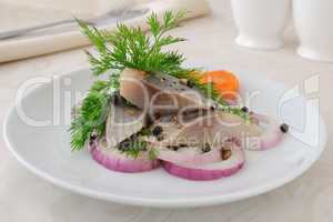 Slices of salted herring with onions and spices
