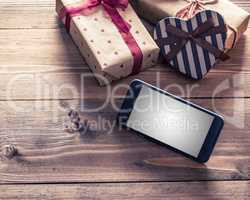 Smart phone near gift boxes. Clipping path included.