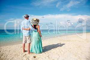 Vacation Couple walking on tropical beach Maldives.