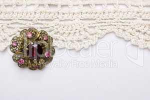 Vintage brooch on lace background