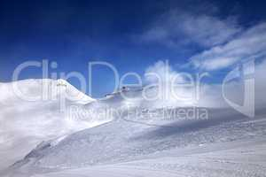 Ski slope with snowmobile trail and mountains in mist at nice da