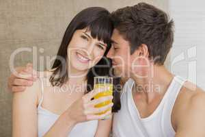 Woman drinking juice while man embracing