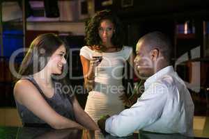 Unhappy woman looking at a couple flirting near bar counter