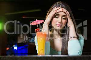 Depressed woman having cocktail drink at bar counter