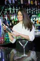 Pretty bartender mixing a cocktail drink in cocktail shaker