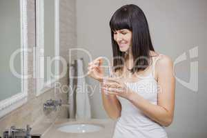 Beautiful woman holding pill and glass of water