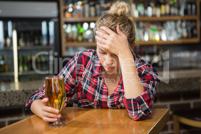 Exhausted woman having a beer